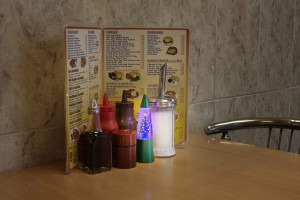 condiments on table of cafe next to christmas decoration